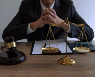 Legal law, advice and justice concept, counselor lawyer or notary working on a documents and report of the important case and wooden gavel, brass scale on table in courtroom.